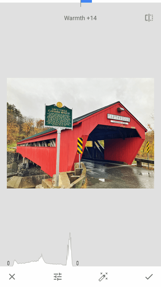 A screenshot of a red covered bridge demonstrating how to tune an image in Snapseed.