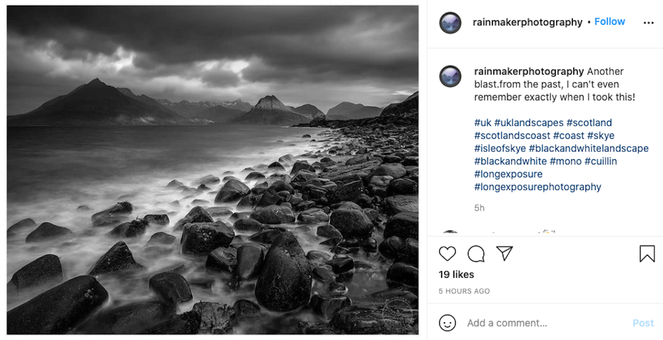 An Instagram screenshot of the ocean in black and white with rocks in the foreground and mountains in the background.