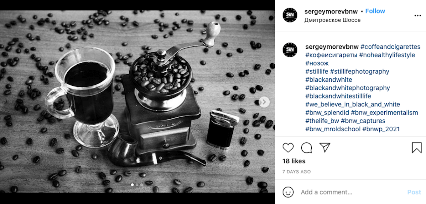 An Instagram screenshot featuring a black-and-white photo of a cup of coffee, a coffee grinder, and coffee beans.