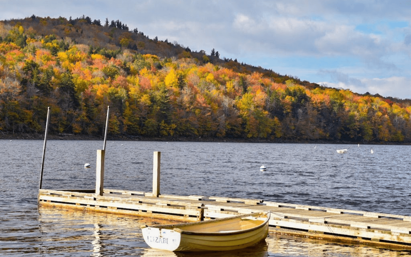 A photo of a small boat moored next to a dock, demonstrating the use of foreground, middle-ground, and background in photography.