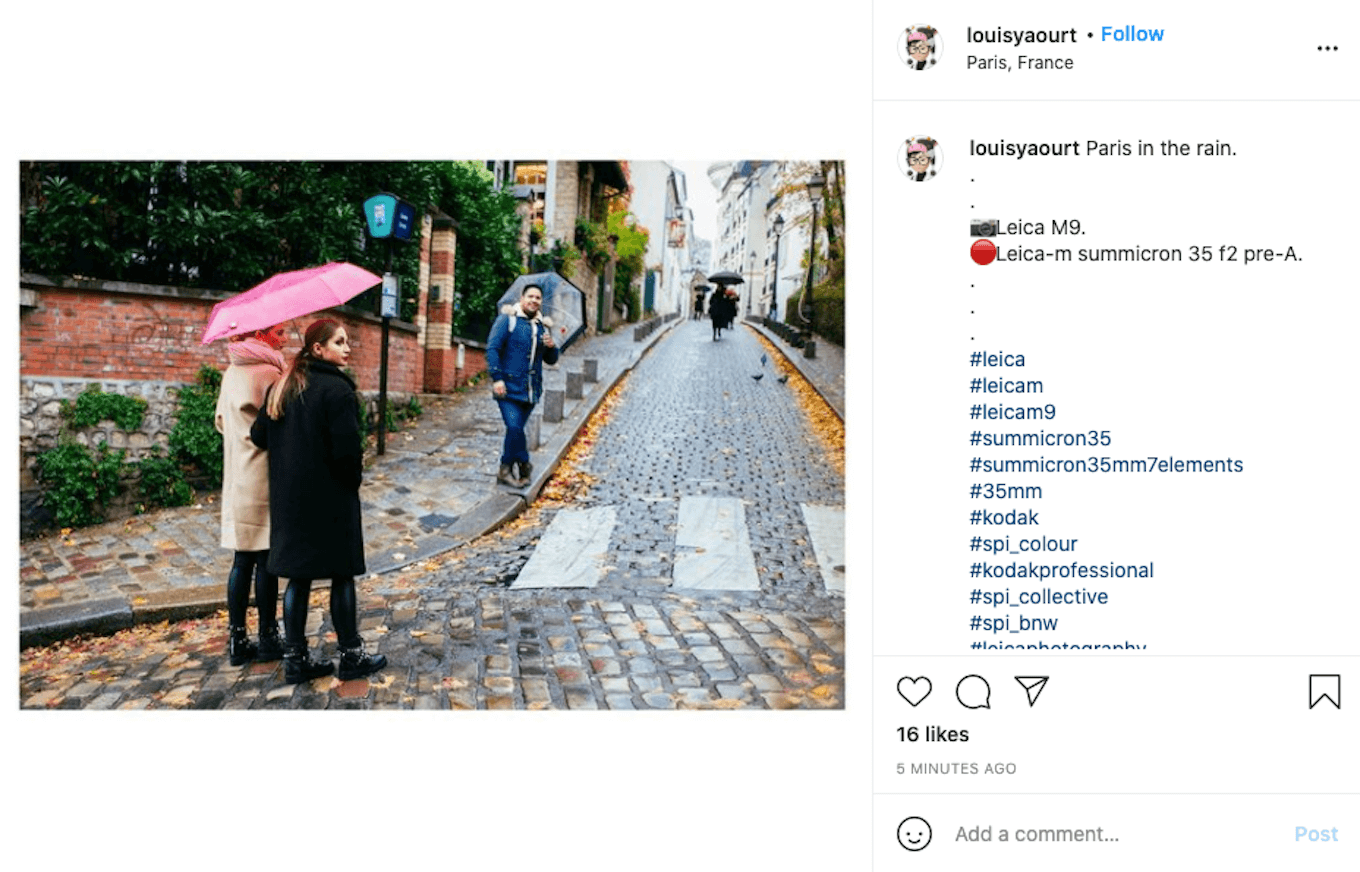 An Instagram screenshot showing several people walking with umbrellas in the rain.