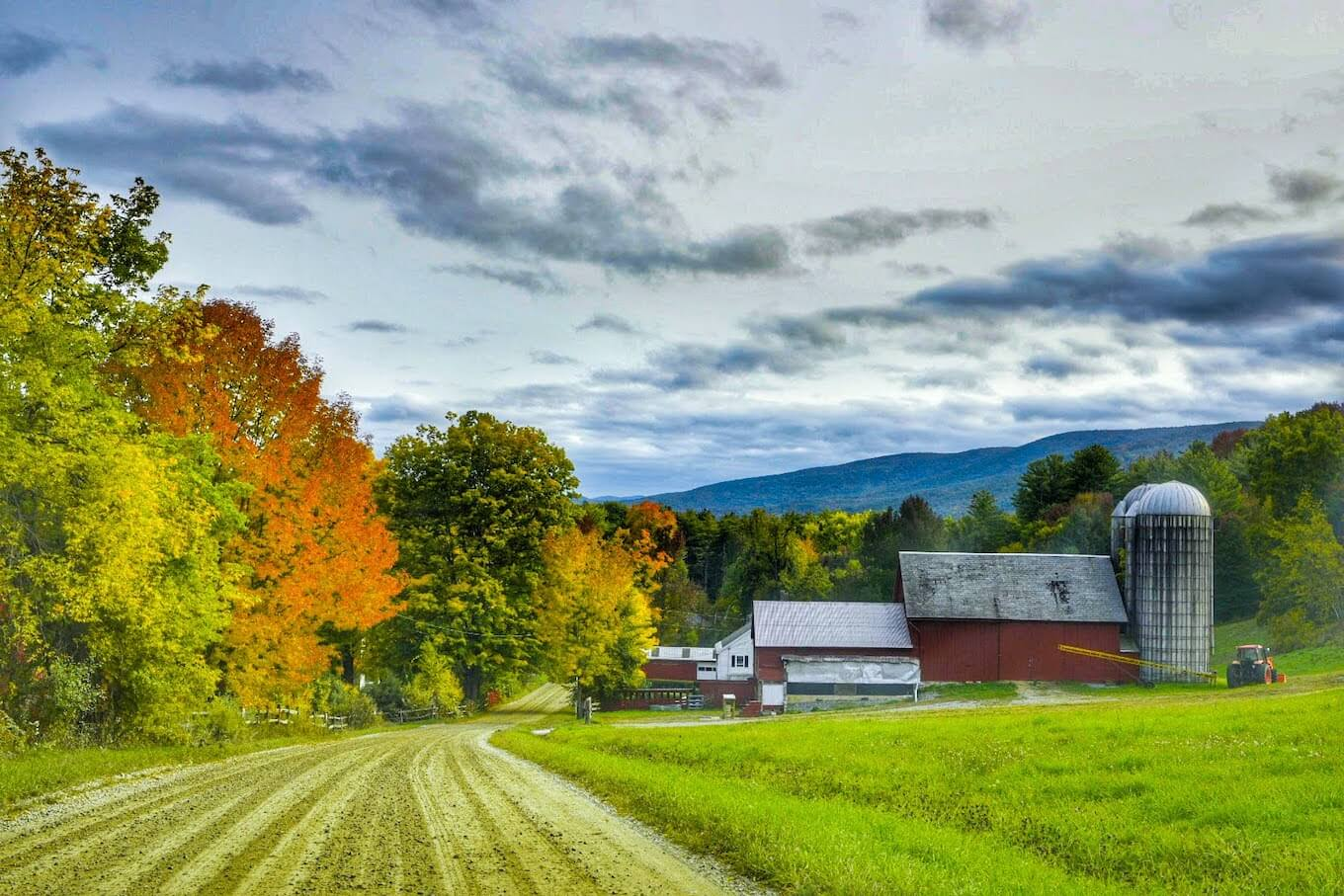 A photo of a red barn near a dirt road in the country, used to demonstrate how to create balance within a photograph.