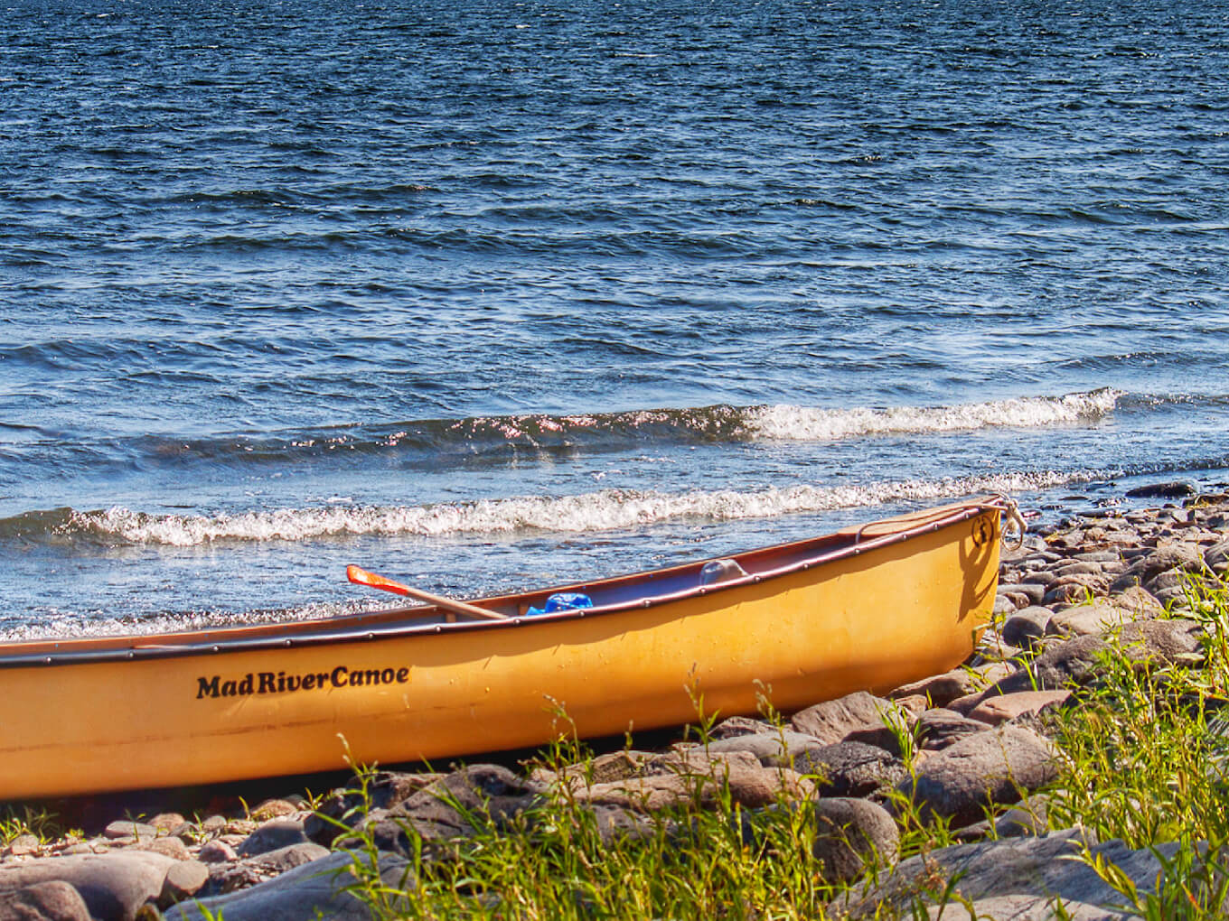 A yellow canoe on the shore of a blue lake demonstrates color contrast in photography.